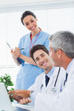 Happy nurse listening to doctors talking about something on thei Stock Photo