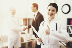 Happy nurse in medical dressing gown with stethoscope and folder shows thumb up. stock photo