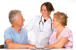 Happy nurse and patients. Cute nurse stands near the old couple Stock Photos