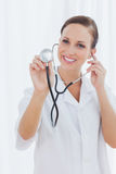 Happy nurse posing holding her stethoscope Stock Photography
