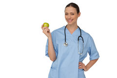 Happy nurse in scrubs holding green apple Stock Photo
