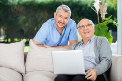 Happy Nurse And Senior Man With Laptop. Portrait of happy male nurse and senior men with laptop on couch at nursing home porch stock image