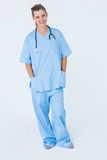 Happy nurse smiling at camera with hands in pockets Stock Images
