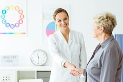 Happy nutritionist and client. Happy nutritionist in white uniform shaking hand of her client in her office Royalty Free Stock Photography