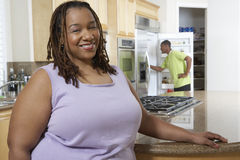 Happy Obese Woman At Kitchen Counter. Portrait of an obese African American women smiling with boy in the background Royalty Free Stock Photography