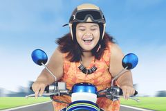 Happy obese woman riding a scooter. Picture of happy obese woman closing her eyes while riding a scooter on the highway Stock Images