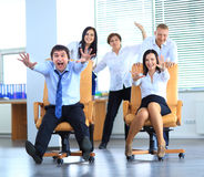 Happy office employees having fun at work. In an office chair race royalty free stock photo
