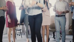 Happy office employees hold a physical activity. Young multiethnic colleagues celebrating, playing with soccer ball 4K. Mixed ethnicity people stand in circle stock footage
