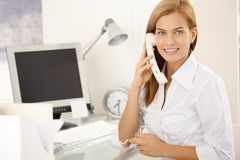 Happy office girl on landline phone call. Sitting at desk, smiling at camera Stock Images