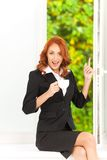 Happy office girl sitting on windowill. Royalty Free Stock Photography