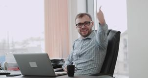Happy office manager smiling in front of the camera and showing a big like sitting on his office chair. 4k. Happy office manager smiling in front of the camera stock video footage
