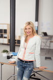 Happy Office Woman Leaning Against her Desk Stock Image