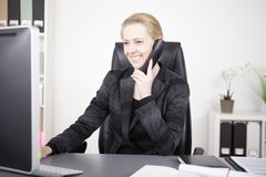 Happy Office Woman Talking to Someone on Phone. Happy Adult Office Woman at her Office Talking to Someone on Telephone While Looking at her Computer Screen Stock Photo