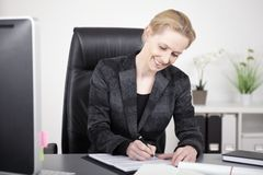 Happy Office Woman Writing a Document at her Table Royalty Free Stock Image