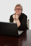 Happy office worker. Short hair blond caucasian woman sitting at desk in front of a laptop computer wearing with a happy excited facial expression looking up stock photos