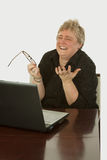 Happy office worker. Short hair blond caucasian woman sitting at desk in front of a laptop computer with a happy excited expression royalty free stock images