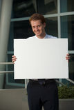 Happy Office Worker Behind Blank Sign Vertical. A happy and smiling office worker holding a blank sign outside of a glass office building.  20s handsome Royalty Free Stock Photography