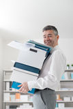 Happy office worker carrying boxes stock photo