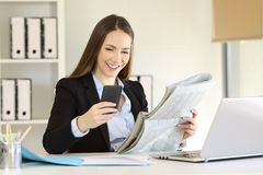 Office worker checking phone and newspaper. Happy office worker checking smart phone content and newspaper Royalty Free Stock Photo