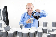 Happy office worker drinks too much coffee Royalty Free Stock Images
