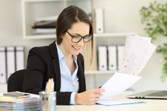 Happy office worker with eyeglasses comparing documents. Happy office worker wearing eyeglasses comparing paper documents stock photos