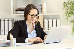 Happy office worker with eyeglasses working online. Happy office worker wearing eyeglasses working online writing in a laptop royalty free stock images