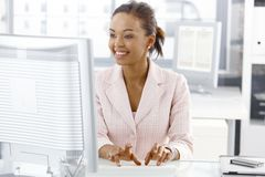 Happy office worker girl at desk stock image