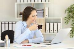 Office worker having a coffee break looking away Royalty Free Stock Image