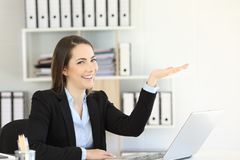 Office worker holding something looking at you. Happy office worker holding something with her palm looking at you Royalty Free Stock Photography