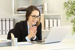 Happy office worker receiving good online news. In a laptop Stock Photo
