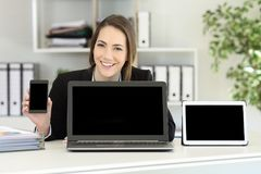 Office worker showing multiple device blank screens. Happy office worker showing multiple device blank screens on a desktop royalty free stock photography