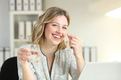 Happy office worker showing a vitamin supplement pill. And a water glass looking at camera Stock Photos