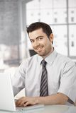 Happy office worker sitting at desk using laptop Royalty Free Stock Photography