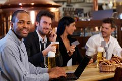Happy office worker using laptop at bar Royalty Free Stock Photography
