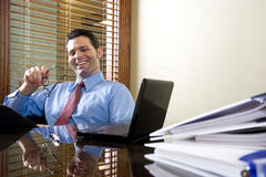 Happy office worker working on laptop computer Stock Photo