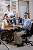 Happy office workers meeting at table in boardroom Stock Photos
