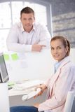 Happy office workers smiling in office. Happy casual office workers smiling in bright office royalty free stock photography
