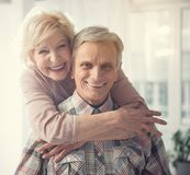 Glad mature couple standing in embrace. Happy old age. Portrait of hugging pensioners looking at camera with broad smile Royalty Free Stock Images