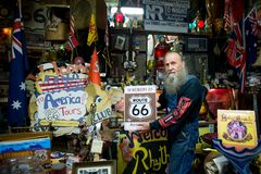 Typical face of an old american on Route 66 posing with the Route 66 sign. Happy old american man indoors posing with Route 66 sign royalty free stock image