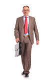 Happy old businessman with briefcase walking forward Royalty Free Stock Photo