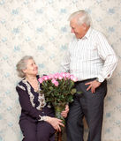Happy old couple and big bouquet of pink roses. Grandmother siting, gtanfather stay near and smile. at home Stock Photo