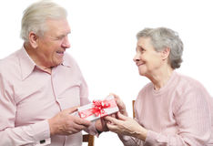 Happy old couple and box with gift. On white background Royalty Free Stock Photo