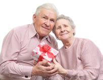 Happy old couple and box with gift. On white background Stock Photography