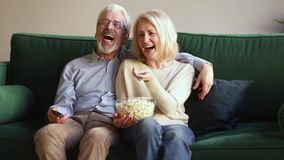 Happy old couple holding remote control laughing watching tv show