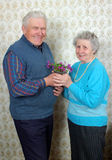 Happy old couple with natural flowers. At home Royalty Free Stock Image