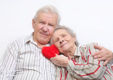 Happy old couple with red heart royalty free stock photography