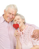 Happy old couple with red heart-shaped candy Royalty Free Stock Image