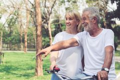 Happy old couple riding a bicycle in the park. Happy senior couple riding a bicycle in the park stock photo