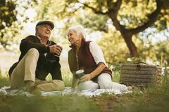 Senior couple sharing few precious memories on picnic. Happy old couple sitting on blanket at the park having coffee and sharing few precious memories. Old stock images