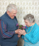 Happy old couple smell flowers. At home Stock Image